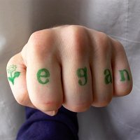 hand with the word 'vegan' written on the fingers